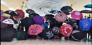 Estudiantes se manifiestan con sombrillas en un centro comercial
