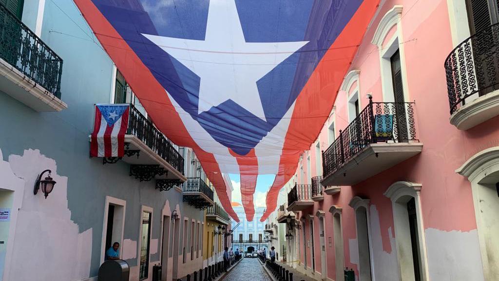 Develan bandera puertorriqueña en la Calle Fortaleza